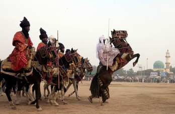 Men dressed in traditional clothes ride horses during the Durbar festival in Kano November 28, 2009. The Durbar is a traditional horse-riding festival hosted by the Emir of the northern city of Kano to mark the Eid al-Adha Muslim celebration. Groups of horsemen representing nearby villages take turns to charge towards the Emir, pausing before him to pay their respects. REUTERS/Goran Tomasevic (NIGERIA SOCIETY RELIGION IMAGES OF THE DAY)